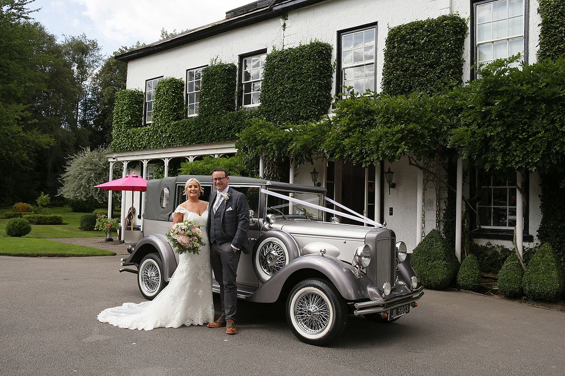 bride and groom stood next to silver grey vintage wedding car outside statham lodge hotel