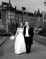 bride and groom walking on path with arley hall in background
