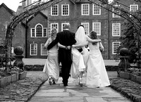 bride and groom walking away with bridesmaids showing back of dresses
